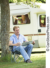 Man Relaxing Outside Mobile Home On Vacation