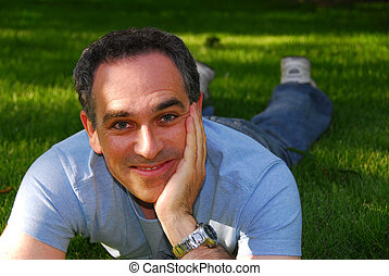Man relaxing outside on green grass
