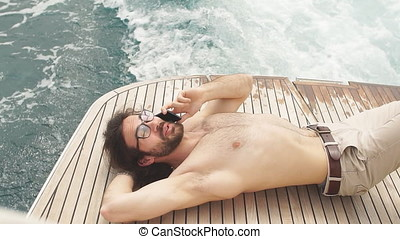 Man relaxing under the sun, lying on a boat at sea. Luxury...