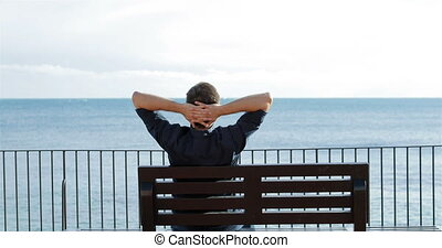 Man relaxing watching ocean on a bench