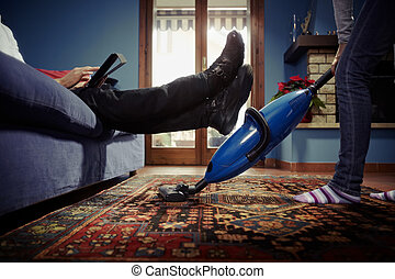 caucasian heterosexual couple, with woman doing chores using vacuum cleaner on carpet and lazy man on sofa with tablet pc. Horizontal shape, low angle view