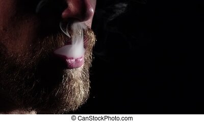 Man releases smoke from mouth. Black. Silhouette. Slow motion