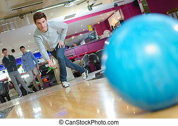 Man releasing bowling ball