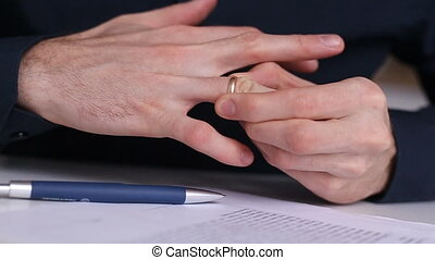 man removes a wedding ring from his finger from his hand and leaves it on the table. Divorce agreement on table