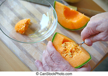 Man removes seeds from cantaloupe closeup