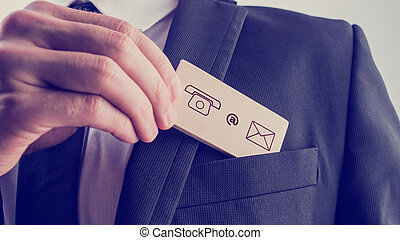 Man removing a card with contact icons from the pocket of his ja