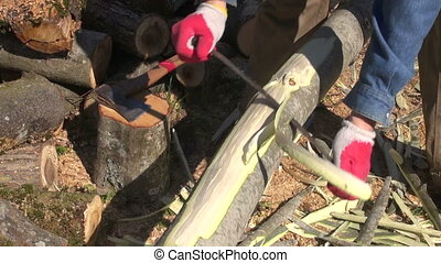 Man removing bark from young tree trunk - Man wearing red...