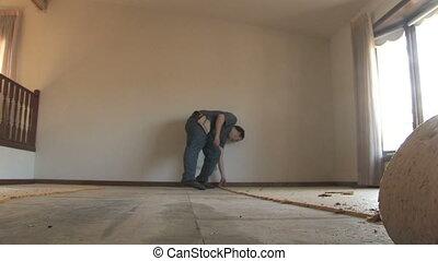 Man Removing Carpet - A handyman tears up carpet padding...