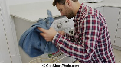 Man removing cloths from washing machine in a comfortable ...
