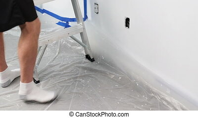 Man Removing Painters Tape and Plastic Tarp After Painting