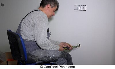 Man removing wire insulation with stripper tool. Electrician connecting rosettes