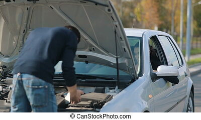 Man repair broken car for a woman