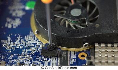 man repair laptop motherboard with screwdriver. remove...