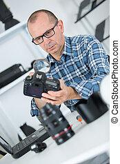 man repairing a camera at his workplace
