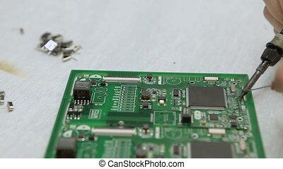 Man repairing a chip soldering iron, close-up