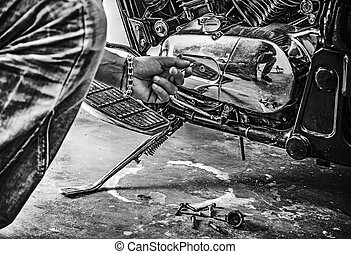 man repairing a classic motorcycle in black and white