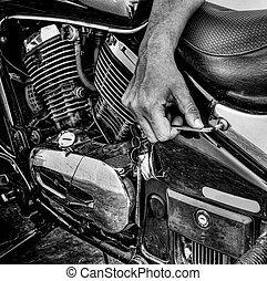 man repairing a classic motorcycle in hdr in black and white