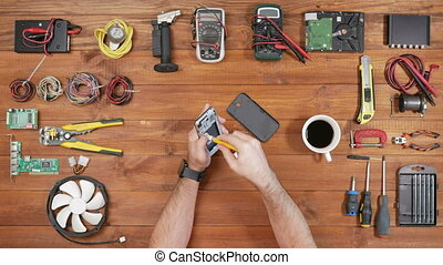 Man repairing a mobile phone. Checks parts inside the device. Wooden table top view
