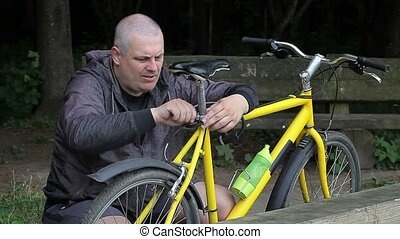 Man repairing bicycle in the park