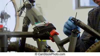 Man repairing bicycle in workshop 4k - Attentive man ...
