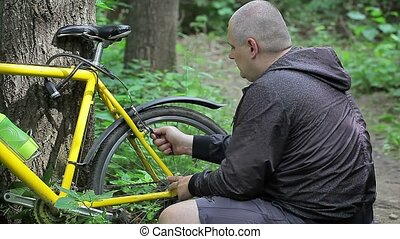 Man repairing bicycle near tree in forest