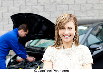 Man repairing car of smiling woman