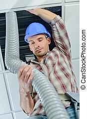 Man repairing ceiling ventilation