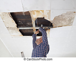 Man repairing collapsed ceiling. Ceiling panels damaged huge hole in roof from rainwater leakage. Water damaged ceiling .