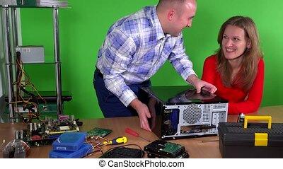 Man repairing computer of his colleague office girl. Beautiful woman flirting