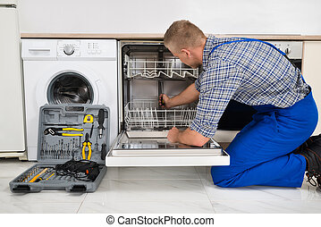 Man Repairing Dishwasher - Young Man In Overall With Toolbox...