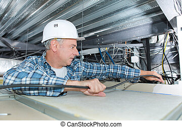 man repairing electrical wiring on the ceiling