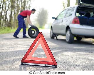 man repairing his car and a flat tire