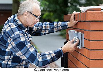 Man repairing intercom at the gate