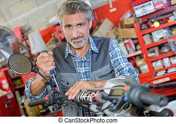 man repairing motorbike in a garage