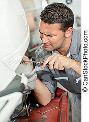 man repairing scooter