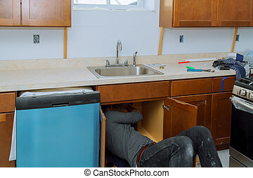 Man repairing sink pipe in the kitchen plumber fitting pipes