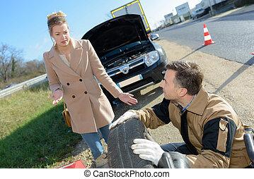 Man repairing woman's puncture beside the road