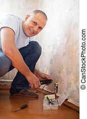 man repairs the socket