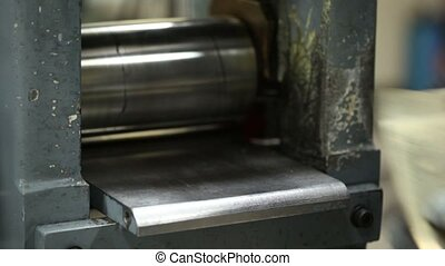 Man repeatedly inserts a metal plate in the rolling machine