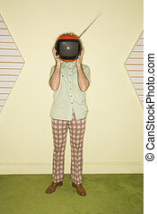 Caucasian mid-adult man wearing vintage clothing holding round red retro television in place of head.