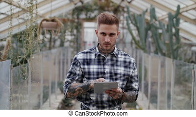 Man researcher standing in greenhouse in botanical garden, using tablet.
