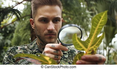 Man researcher with magnifying glass in botanical garden, exploring plants.