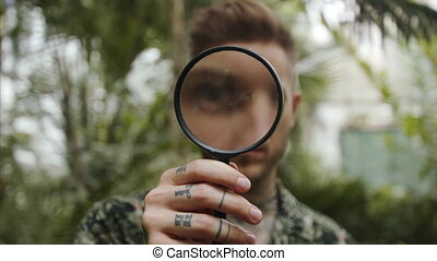 Man researcher with magnifying glass in botanical garden. - ...