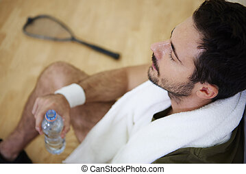 Man resting after practice at squash