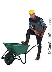 Man resting foot on wheelbarrow