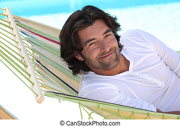 Man resting in hammock next to swimming pool