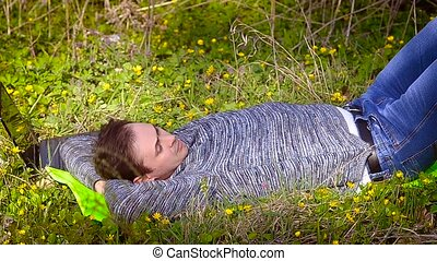 Man resting lying on a blossoming meadow