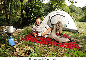 Man resting on a checkered blanket and holding a cup in his hands
