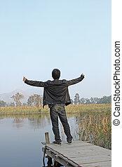 Man resting on a pontoon by a lake
