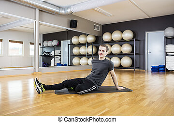 Man Resting On Exercise Mat In Gym